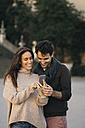 Laughing couple looking at cell phone - KKAF00118