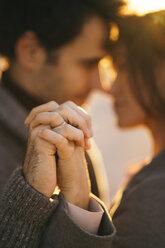 Couple holding hands at sunset, close-up - KKAF00139