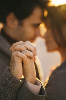 Couple holding hands at sunset, close-up - KKAF00139