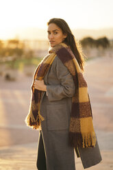 Portrait of woman wearing coat and long scarf - KKAF00142