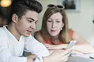 Teenage boy using cell phone with woman in background - TAMF00888