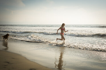Mexico, Riviera Nayarit, Woman running with dog at the beach - ABAF02098