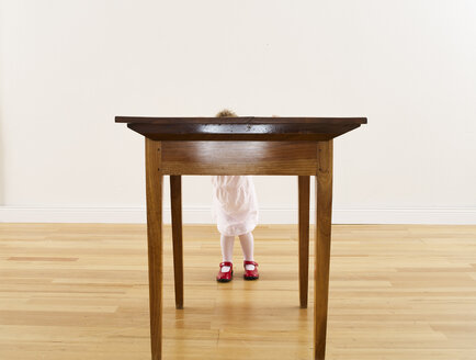 Little girl hiding behind wooden table - FSF00606