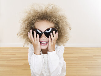 Portrait of smiling girl with blond ringlets wearing oversized sunglasses - FSF00639