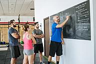 Coach in a fitness class writing on blackboard - KIJF00909