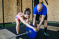 Man and woman preparing barbell in gym - KIJF00915