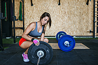 Woman preparing barbell in gym - KIJF00918