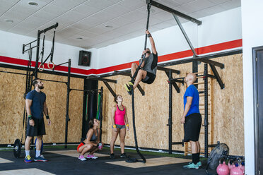 Group of athletes watching man climbing a rope in gym - KIJF00927