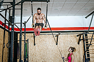 Man doing exercises on rings in gym with woman assisting - KIJF00939