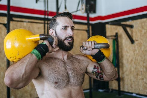 Man lifting kettlebells in gym - KIJF00945