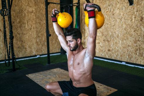 Man lifting kettlebells in gym - KIJF00948