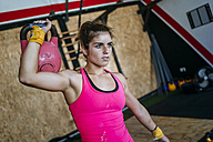 Woman lifting kettlebell in gym - KIJF00951