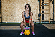 Woman preparing to lift kettlebell in gym - KIJF00954