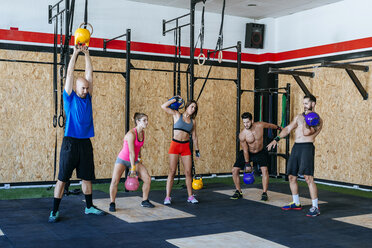 Group of athletes lifting kettlebells in gym - KIJF00957