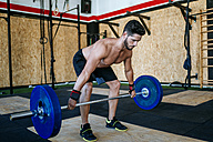 Man lifting barbell in gym - KIJF00960