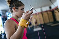 Close-up of woman holding skipping rope in gym - KIJF00963