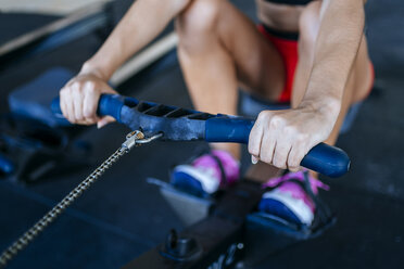 Close-up of woman exercising with a rowing machine in gym - KIJF00966