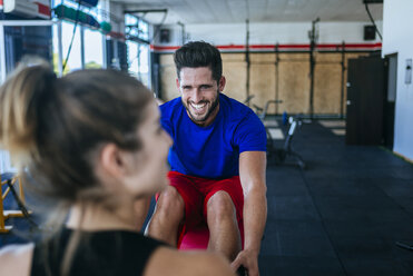Smiling man looking at woman in gym - KIJF00969