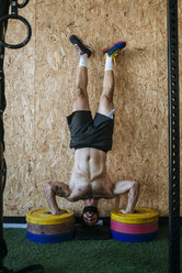 Man doing a handstand on weights - KIJF00978
