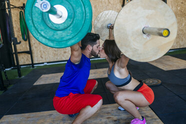 Couple kissing while lifting barbells in gym - KIJF00981