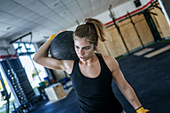 Woman exercising with ball in gym - KIJF00984