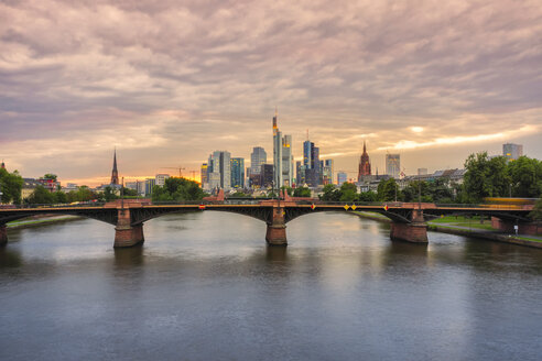 Germany, Frankfurt, view to financial district at sunset with Ignatz-Bubis-Bridge in the foreground - KRPF02060