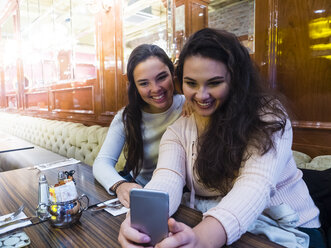 Two young women taking selfie with cell phone in a restaurant - AMF05119