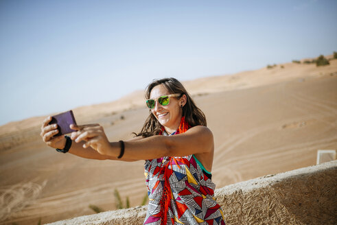 Morocco, Merzouga, smiling torist taking selfie with smartphone - KIJF00992
