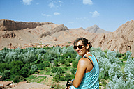 Morocco, Midelt, portrait of smiling woman in front of Draa valley - KIJF01001