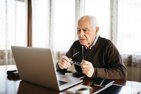 Senior photographer looking at laptop at home - JRFF01053