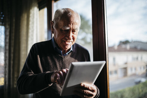 Senior man with tablet standing in front of window at home - JRFF01062