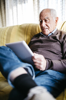 Senior man sitting on couch using tablet - JRFF01065