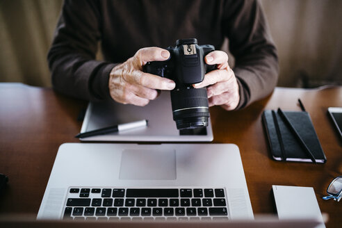 Senior photographer with laptop and digital camera at home, partial view - JRFF01068