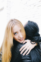 Portrait of young woman hugging her friend in front of white brick wall - GEMF01282