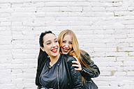 Two laughing young women in front of white brick wall - GEMF01285