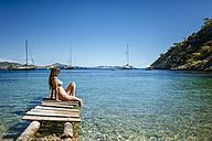 Spian, Ibiza, Woman in bikini sitting on jetty - KIJF01012