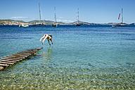 Spian, Ibiza, Woman in bikini jumping from jetty - KIJF01015