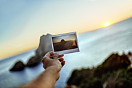 Hand holding image of Es Vedra Island, Ibiza , Spain - KIJF01024