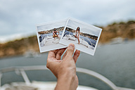Spain, Ibiza, Hand holding images of man and woman on motor boat - KIJF01030