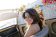Happy woman siting in covertible - KIJF01036