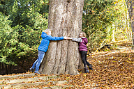 Two children hugging tree in autumn - SARF03077