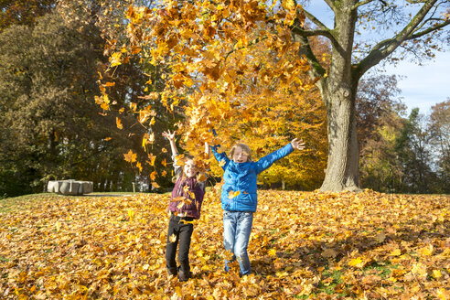 Brother and sister throwing autumn leaves in the air - SARF03080