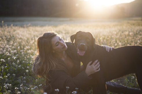 Young woman and her dog in field of flowers at twilight - SKCF00223
