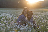 Young woman and her dog in field of flowers at twilight - SKCF00229