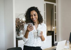 Businesswoman in office using smart phone, holding cup of coffee - EBSF01936