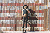 Young woman standing in front of striped wall - GIOF01643