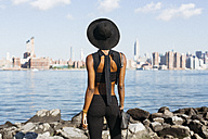 USA, New York City, Brooklyn, young woman standing at East River - GIOF01646