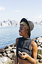USA, New York City, Brooklyn, smiling young woman at East River with cell phone - GIOF01649