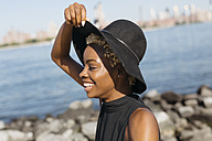 USA, New York City, Brooklyn, smiling young woman at East River wearing a hat - GIOF01652