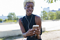 Smiling young woman with cell phone and earbuds - GIOF01661
